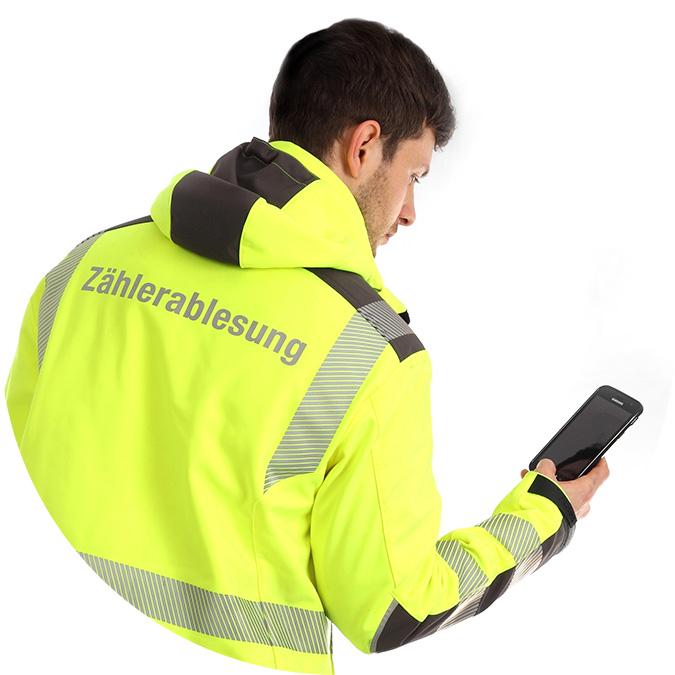 """Mann mit gelber Jacke mit Aufschrift """"Zählerablesung"""" und einem Smartphone in der Hand"""