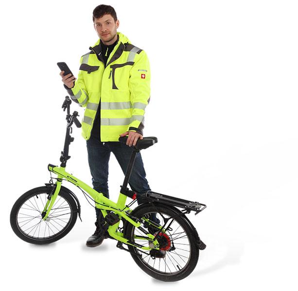 RZ-Messdienste Mitarbeiter steht hinter einem Klappfahrad mit einem Handy in der Hand und blickt zur Kamera